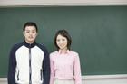 黒板の前に立つ学生 男女2人