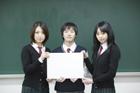 ホワイトボードを持つ学生 男女3人