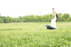 新緑の草原に座り伸びをする女性