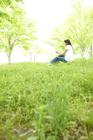 新緑の草原で音楽を聴く女性