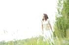 新緑の草原に立つ女性
