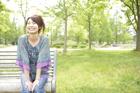 新緑の公園でベンチに座る女性