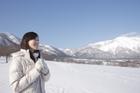 雪原と雪山の山並みと女性