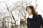 冬の木立とコートを着た笑顔の女性