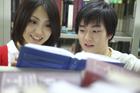 図書室で本を読む学生カップル