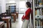図書室の本棚に寄りかかる学生