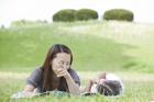 芝生に寝転ぶ母親と娘