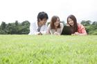 草原でノートパソコンを見る若者達