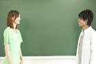 黒板の前の向い合う学生カップル