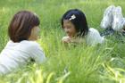 草原に寝転び向い合う母親と娘