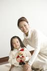 クマのヌイグルミを持つ女の子と母親