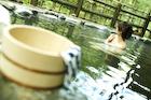 露天風呂の桶と手拭いと女性