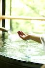 温泉の湯をすくう女性の手