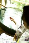 温泉の湯をすくう女性