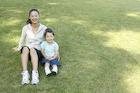 芝生に座る母親と女の子