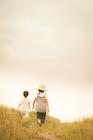 野原を歩く2人の子供の後姿