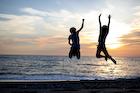 夕焼けの砂浜でジャンプする2人の若い男性