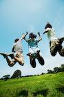 草原でジャンプする若者たち