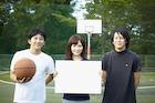 バスケットコートでメッセージボードを持つ3人の若者達