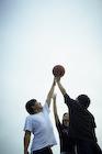 バスケットボールをする3人の若者達