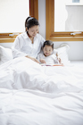 ベッドで本を読む母親と娘