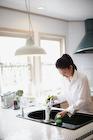 キッチンで野菜を洗う女性