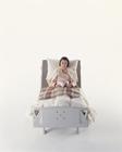 介護ベッドで本を読む中高年女性