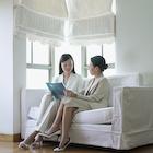 ソファに座って資料を見ている二人のビジネスウーマン