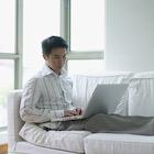 ソファに座ってパソコンで作業しているビジネスマン