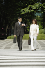 横断歩道を歩くビジネスマンとビジネスウーマン