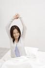 ベッドで伸びをする日本人女性