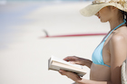 海辺で読書をする日本人女性