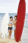 サーフボードを持って海辺に立つ日本人女性