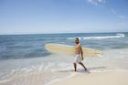 サーフボードを持って海辺を歩くシニア男性