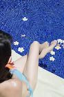 プールサイドに座る日本人女性