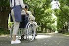 老人が乗った車椅子を押す介護士