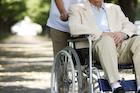 老人が乗った車椅子を押す男性