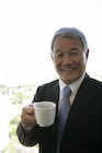 コーヒーカップを持つシニア男性
