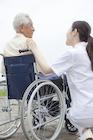 車椅子の男性と会話をする女性介護士
