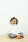 フローリングに座る笑顔の女の子