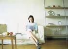 ソファでノートパソコンを打つ女性
