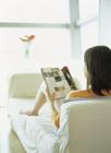 ソファで雑誌を読む女性の後姿