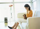ソファで携帯電話で話す女性