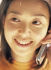 携帯電話で話す女性の顔アップ