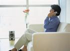ソファで携帯電話で話す男性
