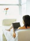 ソファでノートパソコンを打つ女性の後姿