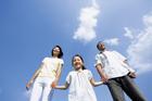 青空の下で手をつなぐ笑顔の3人家族
