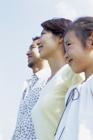 横に並び空を見上げる3人家族