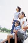 子供を抱え空を見上げる4人家族