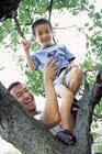 息子を木の枝に上げる父親